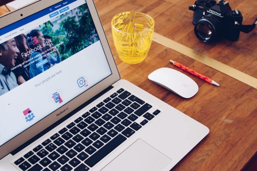 Laptop mit offener Facebookseie. Daneben stehen eine Maus, ein Glas, eine Kamera und ein Stift liegt auf dem Tisch.