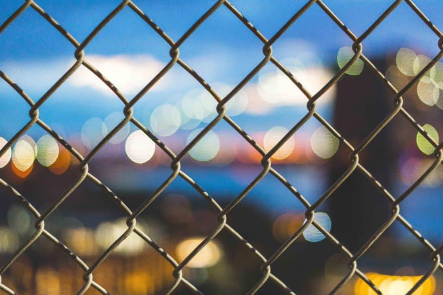 Blick durch einen Zaun auf eine beleuchtete Stadt